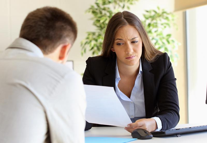 Woman looking suspiciously at a resume wondering if they contain any white lies. See why they matter.